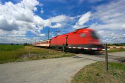 An einem Bahnübergang fährt ein Zug durch