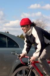 Ein Fahrradfahrer fährt neben einem Auto