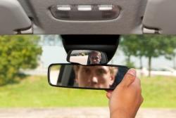 Ein Mann überprüt durch einen Blick in den Rückspiegel ob er Überholen kann