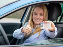 Eine junge Autofahrerin zeigt ihren Führerschein