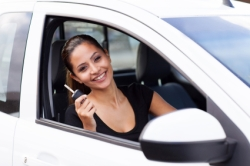Eine junge Autofahrerin zeigt ihren Autoschlüssel