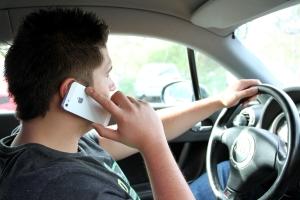 Ein Autofahrer mit Handy am Steuer