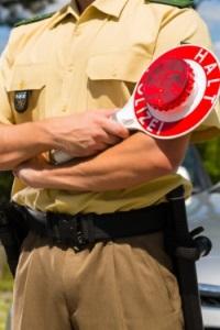 Ein Polizist hät einen Verkehrsteilnehmer für eine Kontrolle an