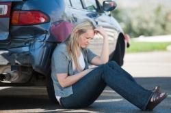 Eine Frau sitzt verzweifelt neben ihrem Auto